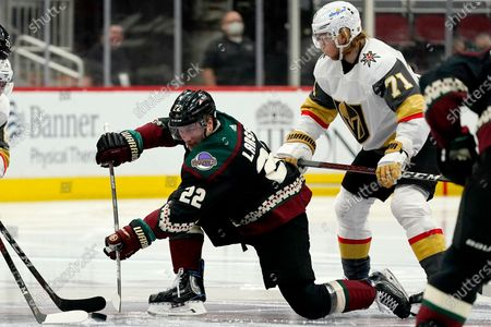 Arizona Coyotes left wing Johan Larsson (22) passes the puck after winning a face-off against Vegas Golden Knights center William Karlsson (71) during the second period of an NHL hockey game, in Glendale, Ariz