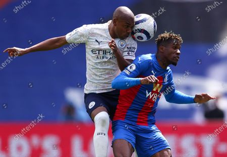 Manchester City's Fernandinho, left, and Crystal Palace's Wilfried Zaha compete for the ball during the English Premier League soccer match between Crystal Palace and Manchester City at Selhurst Park in London, England