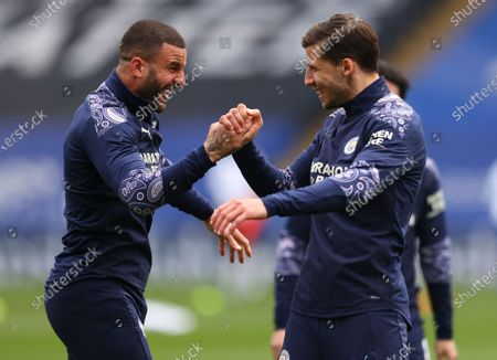 Manchester City's Kyle Walker, left, and teammate Ruben Dias react as they warm up ahead of the English Premier League soccer match between Crystal Palace and Manchester City at Selhurst Park in London, England