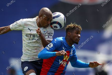 Fernandinho (L) of Manchester City in action against Wilfried Zaha (R) of Crystal Palace during the English Premier League soccer match between Crystal Palace and Manchester City in London, Britain, 01 May 2021.