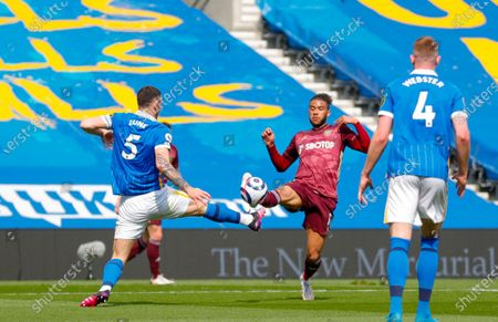 Brighton and Hove Albion defender Lewis Dunk (5) and Leeds United forward Tyler Roberts (11)  during the Premier League match between Brighton and Hove Albion and Leeds United at the American Express Community Stadium, Brighton and Hove