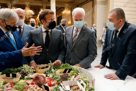 French President Emmanuel Macron (2-L), French Junior Minister of Small and Medium Entreprises Alain Griset (2-R) and French President's gastronomy advisor Guillaume Gomez take part in the traditional Lily of the valley ceremony at the Elysee palace, in Paris, France, 01 May 2021.