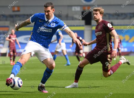 Brighton's Lewis Dunk, left, duels for the ball with Leeds United's Patrick Bamford during the English Premier League soccer match between Brighton and Hove Albion and Leeds United at the Falmer stadium in Brighton, England