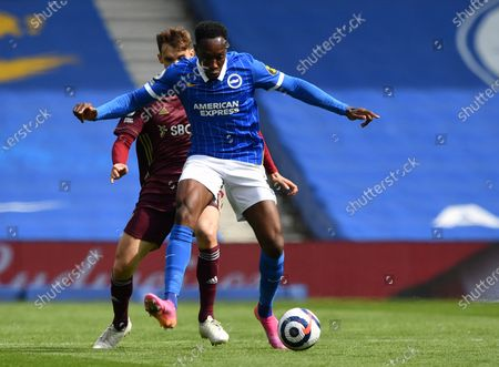 Brighton's Danny Welbeck, front, duels for the ball with Leeds United's Diego Llorente during the English Premier League soccer match between Brighton and Hove Albion and Leeds United at the Falmer stadium in Brighton, England