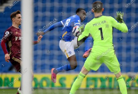 Leeds United's goalkeeper Illan Meslier, right, makes a save in front of Brighton's Danny Welbeck during the English Premier League soccer match between Brighton and Hove Albion and Leeds United at the Falmer stadium in Brighton, England