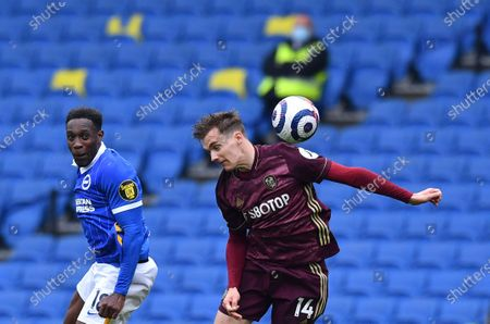 Brighton's Danny Welbeck, left, duels for the ball with Leeds United's Diego Llorente during the English Premier League soccer match between Brighton and Hove Albion and Leeds United at the Falmer stadium in Brighton, England