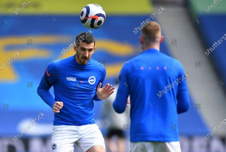 Stock Image of Brighton's Lewis Dunk, left, heads the ball during warm up before the English Premier League soccer match between Brighton and Hove Albion and Leeds United at the Falmer stadium in Brighton, England