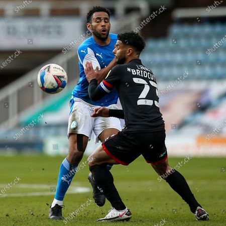 Nathan Thompson of Peterborough United takes on Liam Bridcutt of Lincoln City