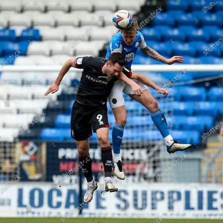 Frankie Kent of Peterborough United challenges Tom Hopper of Lincoln City
