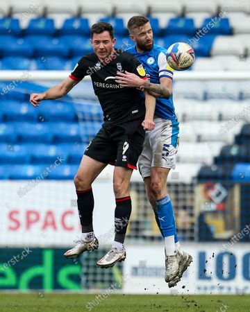 Mark Beevers of Peterborough United challenges Tom Hopper of Lincoln City