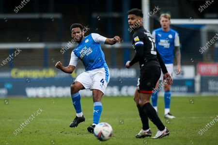 Nathan Thompson of Peterborough United passes the ball past Liam Bridcutt of Lincoln City