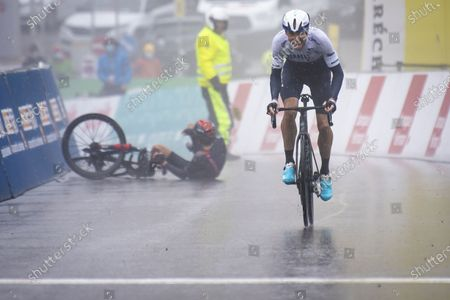 Canadian rider Michael Woods of Israel Start-Up Nation on his way to win as Britain's Geraint Thomas (L) of Ineos Grenadiers falls during the fourth stage of the 74th Tour de Romandie cycling tour, a 161.3 km race from Sion to Thyon-Les Collons, Switzerland, 01 May 2021.