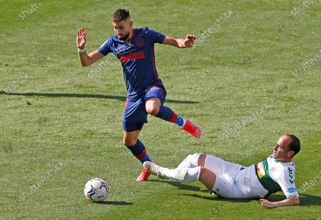 Stock Image of Elche's Juan Francisco Martinez 'Nino' (R) in action against Atletico Madrid's Yannick Carrasco during a Spanish LaLiga soccer match between Elche and Atletico Madrid at Martin Valero stadium in Elche, Alicante, eastern Spain, 01 May 2021.