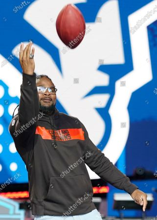 Former Cleveland Browns player Josh Cribbs tosses out a ball to a fan during the sixth round of the NFL football draft, in Cleveland