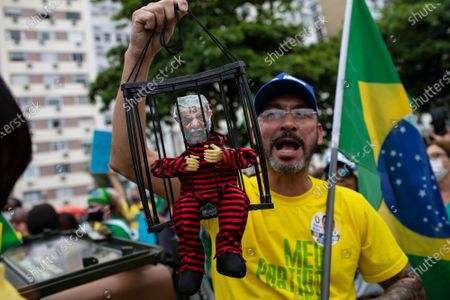 Stock Photo of Man holds an encaged puppet depicting former President Luiz Inacio Lula da Silva in prison clothes, during a demonstration backing President Jair Bolsonaro's anti-coronavirus-lockdown stance, marking May Day, or International Workers' Day, in Rio de Janeiro, Brazil, . Brazil has seen over 400,000 confirmed COVID-19 deaths, a toll second only to the United States