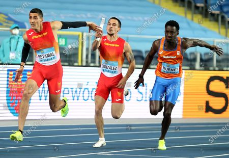 Stock Image of (L-R) Pol Retamal and Jose Gonzalez of Spain and Taymir Burnet of the Netherlands in action during the men's 4x100m relay heats of the World Athletics Relays Championships at the Silesian Stadium in Chorzow, southern Poland, 01 May 2021.