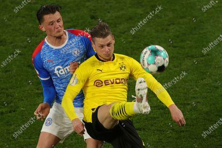 Dortmund's Lukasz Piszczek is challenged by Kiel's Fabian Reese during the German Soccer Cup semifinal match between Borussia Dortmund and Holstein Kiel in Dortmund, Germany