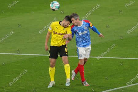 Dortmund's Raphael Guerreiro, left, jumps for a header with Kiel's Fin Bartels during the German Soccer Cup semifinal match between Borussia Dortmund and Holstein Kiel in Dortmund, Germany