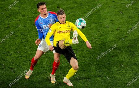 Dortmund's Lukasz Piszczek (R) in action against Kiel's Fabian Reese (L) during the German DFB Cup semi final soccer match between Borussia Dortmund and Holstein Kiel in Dortmund, Germany, 01 May 2021.