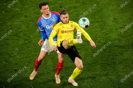 Stock Photo of Dortmund's Lukasz Piszczek (R) in action against Kiel's Fabian Reese (L) during the German DFB Cup semi final soccer match between Borussia Dortmund and Holstein Kiel in Dortmund, Germany, 01 May 2021.