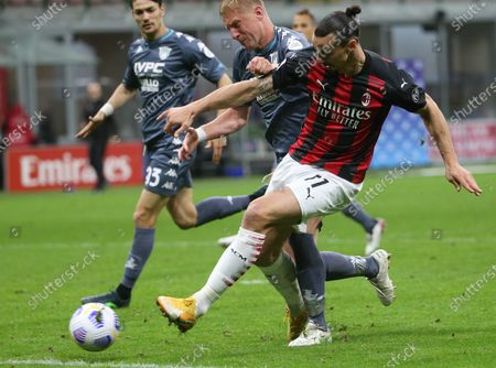 Milan's Zlatan Ibrahimovic (R) in action against Benevento's Kamil Glik (C) during the Italian Serie A soccer match between AC Milan and Benevento Calcio at Giuseppe Meazza stadium in Milan, Italy, 01 May 2021.