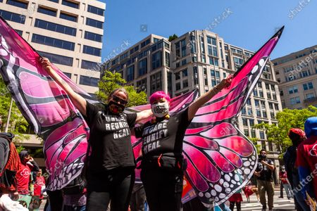 Lariza Dugan Ciara (left) and Ani Rivera wear pink butterfly wings while marching with Caravana para Los Niños (Caravan for the Children) during a large march for immigrant rights and citizenship.