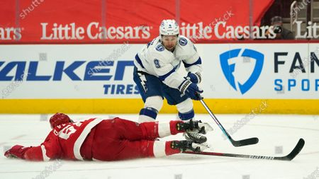 Detroit Red Wings defenseman Danny DeKeyser (65) blocks a Tampa Bay Lightning center Tyler Johnson (9) shot in the first period of an NHL hockey game, in Detroit