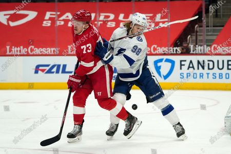 Detroit Red Wings left wing Adam Erne (73) and Tampa Bay Lightning defenseman Mikhail Sergachev (98) battle for the puck in the second period of an NHL hockey game, in Detroit
