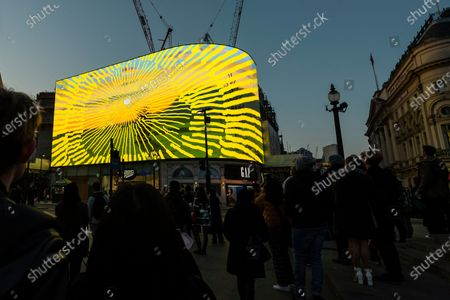 """David Hockney's """"Remember You Cannot Look At The Sun Or Death For Very Long"""" artwork, showing an animated sunrise, is displayed on the giant screens at Piccadilly Circus. It will also be displayed on screens in other cities worldwide including New York, Tokyo and Seoul. The work, created on an iPad, is supposed to offer a symbol of hope as the world awakens from its long lockdown and also coincides with his upcoming """"The Arrival of Spring"""" exhibition at the Royal Academy. In London, the work is on display nightly for the month of May."""