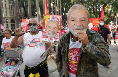 Demonstrator holds a mask depicting former Brazilian President Luiz Inacio Lula da Silva, during a protest against Brazil's President Jair Bolsonaro and his handling of the new coronavirus pandemic, marking May Day, or International Workers' Day, in Sao Paulo, Brazil
