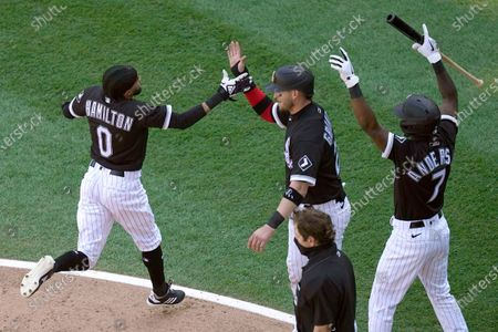 Chicago White Sox's Billy Hamilton, left, Yasmani Grandal, center and Tim Anderson celebrate after Hamilton and Grandal scored on an RBI-double by Leury Garcia during the fourth inning of a baseball game against the Cleveland Indians, in Chicago