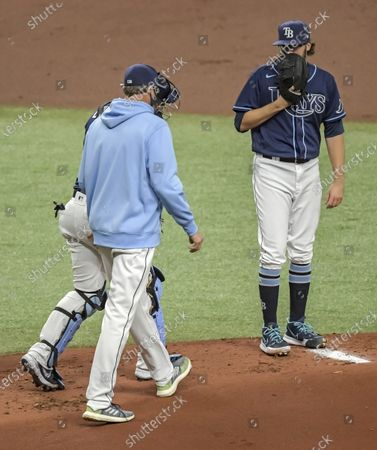 Tampa Bay Rays pitching coach Kyle Snyder, center, and catcher Mike Zunino walk to the mound to talk with starter Josh Fleming, right, after back-to-back walks against the Houston Astros during the first inning of a baseball game, in St. Petersburg, Fla