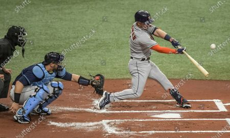 Home plate umpire Chad Fairchild, left, and Tampa Bay Rays catcher Mike Zunino look on as Houston Astros' Alex Bregman hits an RBI-single during the first inning of a baseball game, in St. Petersburg, Fla