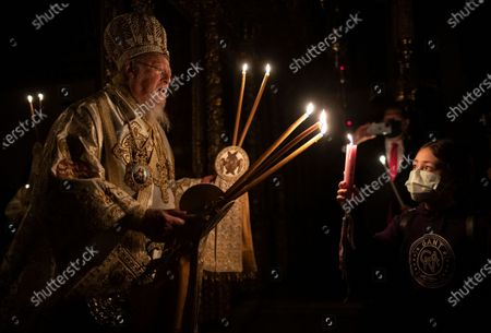 Ecumenical Patriarch Bartholomew I, the spiritual leader of the world's Orthodox Christians, holds candles as he conducts the Easter Resurrection Service with limited attendance as part of the measures to prevent the spread opf the coronavirus, at the Patriarchal Cathedral of St. George in Istanbul, early