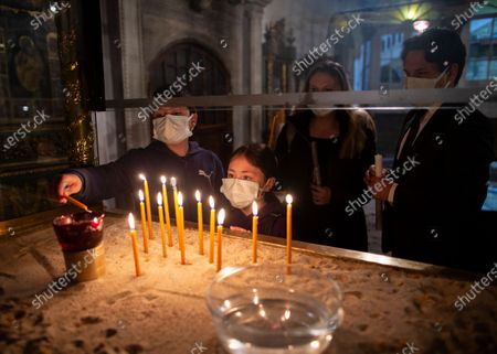 Faithful light candles prior to the Easter Resurrection Service with limited attendance as part of the measures to prevent the spread of the coronavirus, conducted by the Ecumenical Patriarch Bartholomew I, the spiritual leader of the world's Orthodox Christians, at the Patriarchal Cathedral of St. George in Istanbul, late