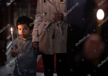 Boy holds a candle as he attends an Easter Resurrection Service with limited attendance as part of the measures to prevent the spread of the coronavirus, conducted by the Ecumenical Patriarch Bartholomew I, the spiritual leader of the world's Orthodox Christians, at the Patriarchal Cathedral of St. George in Istanbul, late