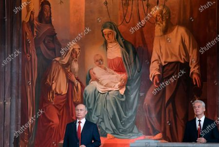 Russian President Vladimir Putin, left, and Moscow's Mayor Sergei Sobyanin, right, attend the Easter service in the Christ the Savior Cathedral in Moscow, Russia, . Eastern Orthodox churches observe the ancient Julian calendar, and this year celebrate the Orthodox Easter on May 2