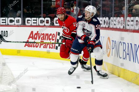Columbus Blue Jackets' Eric Robinson (50) looks to pass the puck as he is shadowed by Carolina Hurricanes' Brett Pesce (22) during the first period of an NHL hockey game in Raleigh, N.C