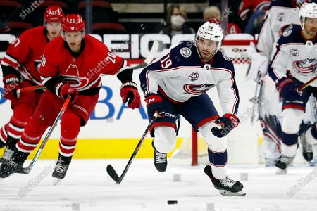 Columbus Blue Jackets' Michael Del Zotto (15) moves the puck up the ice after taking it from Carolina Hurricanes' Sebastian Aho (20) during the third period of an NHL hockey game in Raleigh, N.C