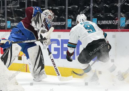 Colorado Avalanche goaltender Devan Dubnyk, left, clears the puck as San Jose Sharks left wing Evander Kane pursues in the first period of an NHL hockey game, in Denver