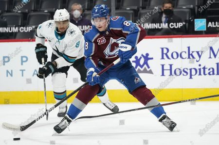 Colorado Avalanche defenseman Cale Makar, front, looks to pass the puck as San Jose Sharks left wing Evander Kane pursues in the second period of an NHL hockey game, in Denver