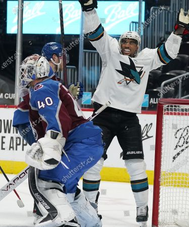 San Jose Sharks left wing Evander Kane, back, elebates after a shot by center Tomas Hertl slipped past Colorado Avalanche goaltender Devan Dubnyk for a goal in the third period of an NHL hockey game, in Denver