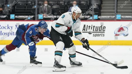 San Jose Sharks left wing Evander Kane, right, drives past Colorado Avalanche defenseman Cale Makar to put a shot on goal in the third period of an NHL hockey game, in Denver