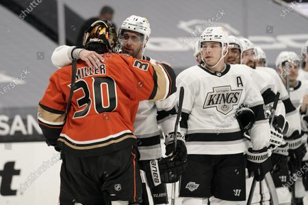 Anaheim Ducks goaltender Ryan Miller, left, is hugged by Los Angeles Kings' Anze Kopitar after an NHL hockey game, in Anaheim, Calif. Miller, who is retiring at the conclusion of the season, played in his final home game