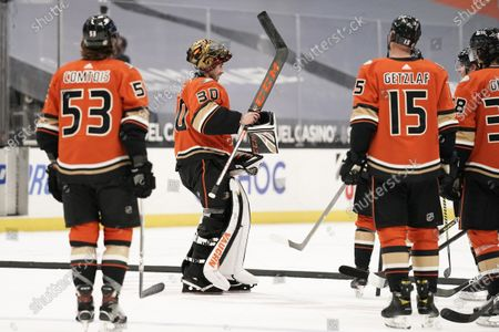 Anaheim Ducks goaltender Ryan Miller, second from left, is surrounded by teammates after an NHL hockey game against the Los Angeles Kings, in Anaheim, Calif. Miller, who is retiring at the conclusion of the season, played his last home game Saturday