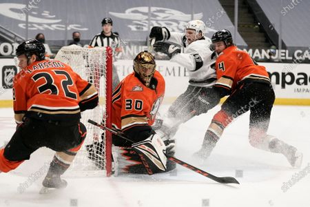 Anaheim Ducks goaltender Ryan Miller, center, guards the net during the third period of the team's NHL hockey game against the Los Angeles Kings, in Anaheim, Calif. The Ducks won 6-2