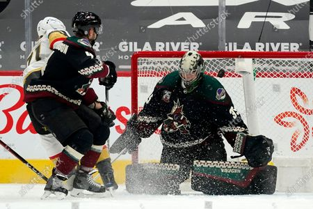 Vegas Golden Knights center William Karlsson, left, scores a goal against Arizona Coyotes goaltender Darcy Kuemper (35) as Coyotes defenseman Niklas Hjalmarsson (4) arrives late to defend during the first period of an NHL hockey game, in Glendale, Ariz