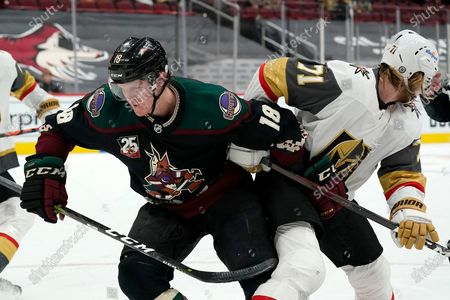 Stock Image of Arizona Coyotes center Christian Dvorak (18) gets tangled up with Vegas Golden Knights center William Karlsson (71) during overtime of an NHL hockey game, in Glendale, Ariz. The Golden Knights defeated the Coyotes 3-2