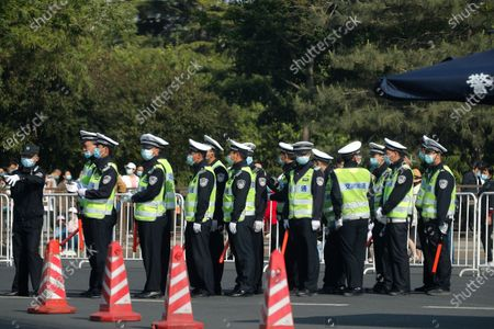 Traffic police wearing face masks to help curb the spread of the coronavirus line up on a street as they preparing for their shift near Tiananmen Square in Beijing, . Chinese tourists are expected to make a total of 18.3 million railway passenger trips on the first day of the country's five-day holiday for international labor day, according to an estimate by the state railway group, as tourists rush to travel domestically after the coronavirus has been brought under control in China