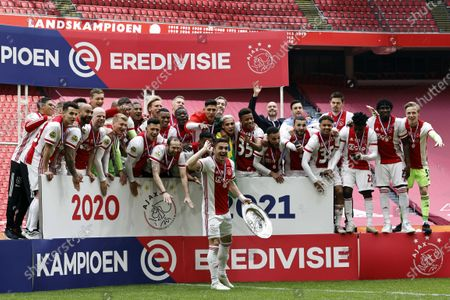 Stock Image of Ajax Amsterdam player Dusan Tadic (C) with the trophy and team-mates celebrate the 35th national championship title after winning the Dutch Eredivisie match between Ajax Amsterdam and FC Emmen at the Johan Cruijff Arena in Amsterdam, Netherlands, 02 May 2021.